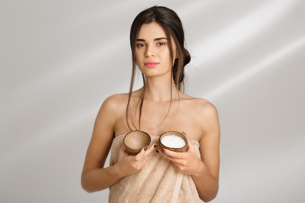 Mulher de toalha hoding sal esfrega. tratamentos de beleza. cuidados com a pele.