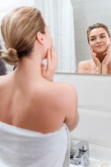 Mulher de toalha olhando no espelho