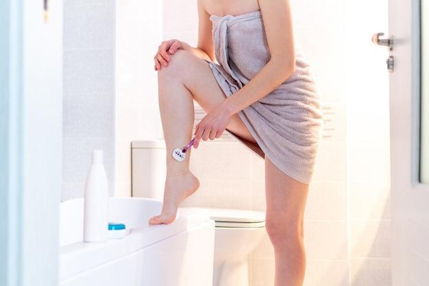 Mulher de toalha raspa as pernas no banheiro com uma lâmina de barbear