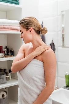 Mulher de toalha rodeada de cosméticos