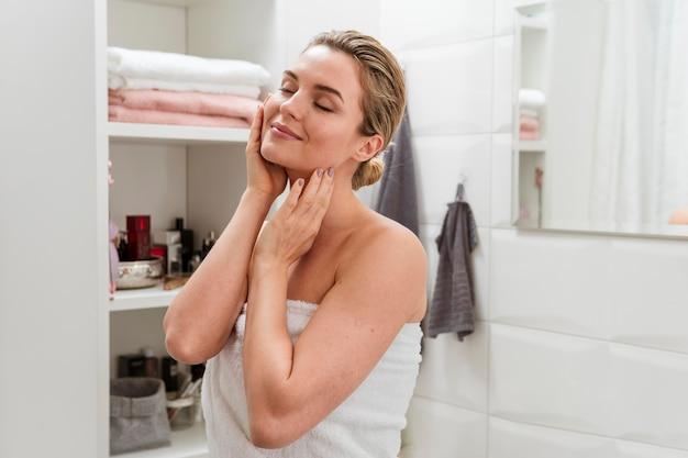 Mulher de toalha tocando seu rosto