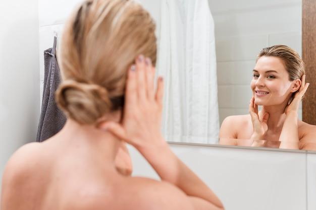 Mulher de toalha, verificando-se no espelho