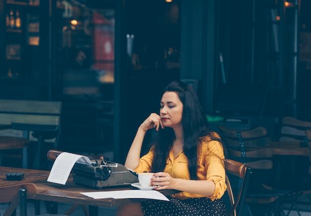 Mulher de top amarelo e saia longa, sentado e tomando café no terraço do café e pensativo durante o dia