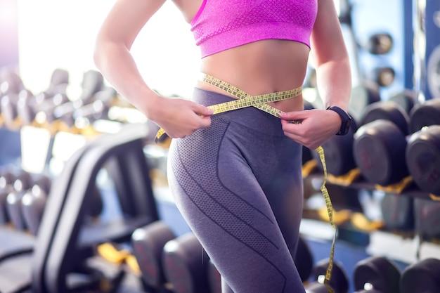 Mulher de top rosa e leggins cinza medindo sua cintura no ginásio. conceito de pessoas, fitness e saúde