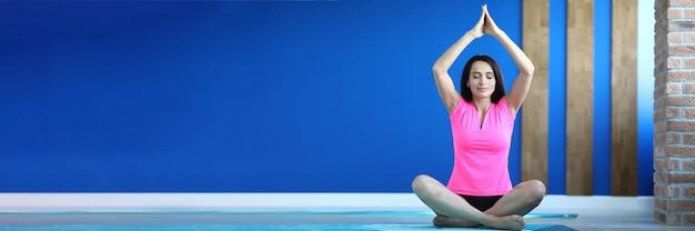 Mulher de top rosa pratica exercícios de ioga na esteira na sala de fitness e alongamento com harmonia.