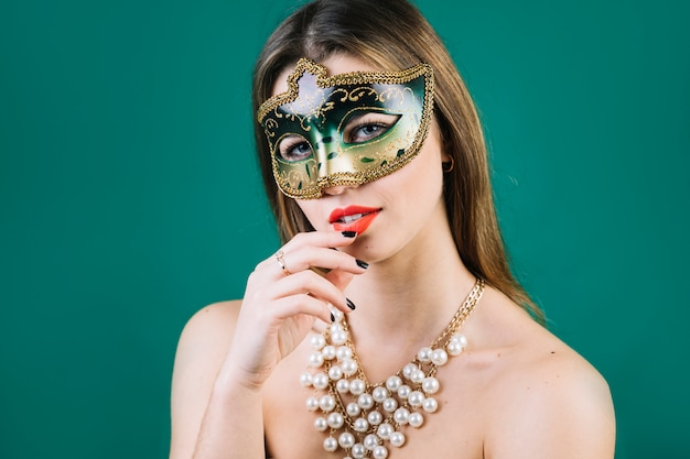 Mulher de topless usando máscara de carnaval de máscaras e colar em pano de fundo verde
