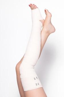 Mulher de tornozelo em um fundo branco arrastado bandagem elástica