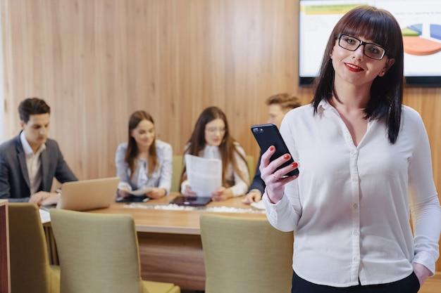 Mulher de trabalhador de escritório elegante em copos com telefone em mãos contra o fundo de colegas de trabalho