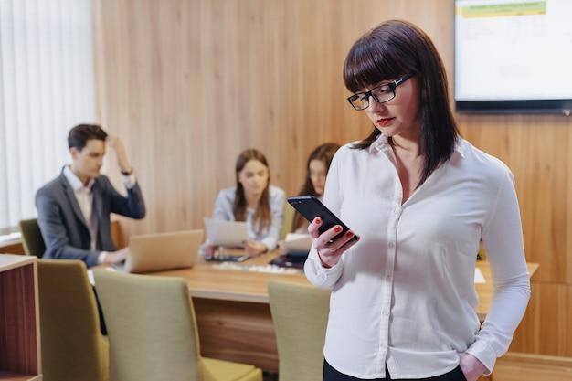 Mulher de trabalhador de escritório elegante em copos com telefone nas mãos