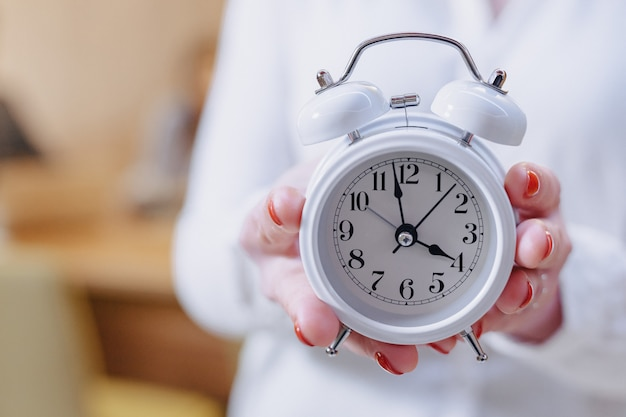 Mulher de trabalhador de escritório elegante em copos com um despertador clássico nas mãos no fundo de colegas de trabalho