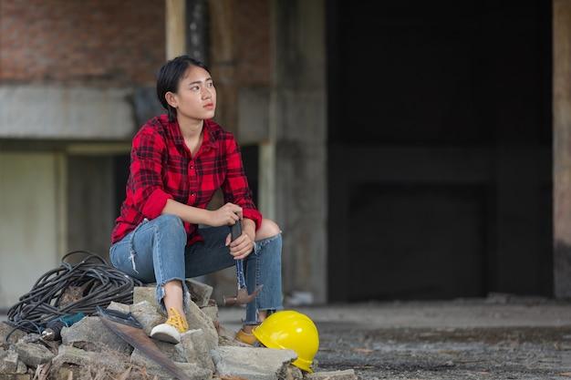 Mulher de trabalhadores sentada e relaxada no canteiro de obras, conceito do dia do trabalho