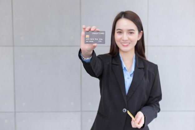 Mulher de trabalho de negócios asiáticos mostra cartão de crédito fechado no conceito de escolha financeira.