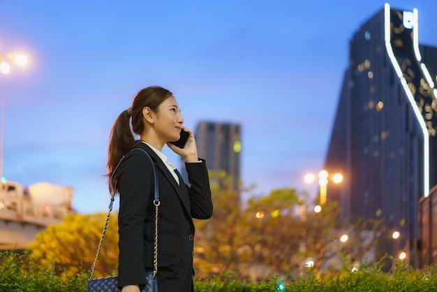 Mulher de trabalho executiva asiática usando um telefone celular na rua com prédios de escritórios em segundo plano à noite em bangkok, tailândia.