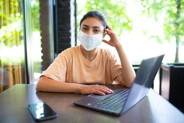 Mulher de treinador de negócios indiano trabalhando em seu laptop ao ar livre.