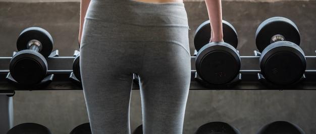 Mulher de treino com levantamento de peso para o corpo magro e corpo magro forma edifício.