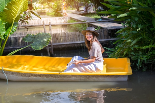 Mulher de turista asiática feliz, passeios de barco para relaxar no the three little pigs organic farm