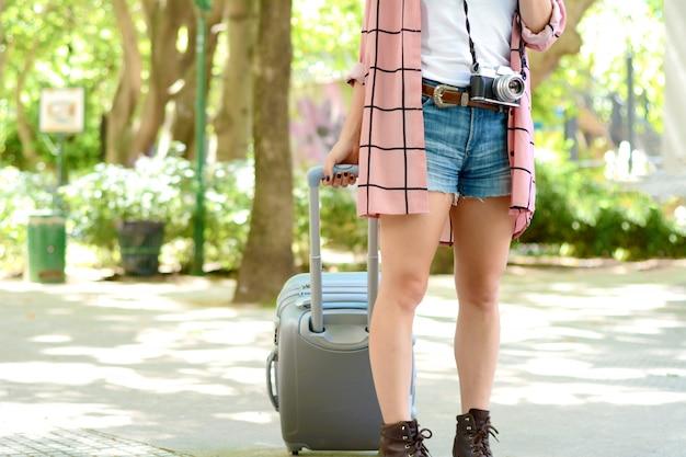 Mulher de turista carregando uma mala na rua