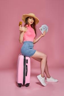Mulher de turista com chapéu de palha de roupas casuais de verão segurando maço de dinheiro e cartão do banco enquanto está sentado na mesa.