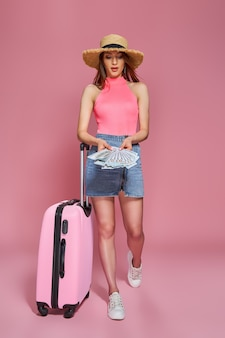 Mulher de turista com chapéu de palha de roupas casuais de verão segurando maço de dinheiro e mala em fundo rosa