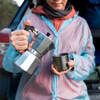 Mulher de turista sênior, derramando café em caneca de metal