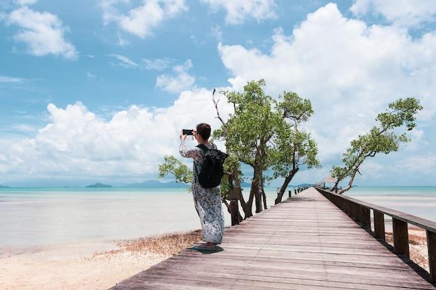 Mulher de turista usando celular tirando foto do oceano na ponte de madeira.