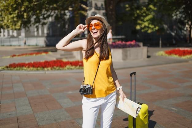 Mulher de turista viajante alegre em óculos de coração laranja com câmera de foto vintage retrô de mapa de cidade mala na cidade ao ar livre. garota viajando para o exterior para viajar no fim de semana. estilo de vida da viagem de turismo.
