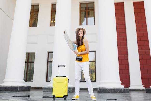 Mulher de turista viajante alegre em roupas casuais com mala, câmera fotográfica vintage retrô segurar mapa da cidade na cidade ao ar livre. garota viajando para o exterior para viajar no fim de semana. estilo de vida da viagem de turismo.