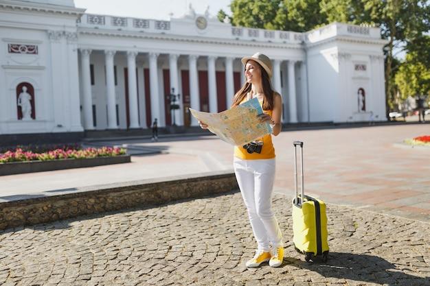 Mulher de turista viajante alegre em roupas casuais de verão amarelo, chapéu com mala segurando o mapa da cidade olhando de lado na cidade ao ar livre. garota viajando para o exterior na fuga de fins de semana. estilo de vida da viagem de turismo.