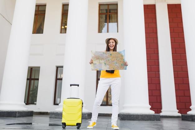Mulher de turista viajante alegre no chapéu de roupas casuais de verão amarelo com mala, olhando no mapa da cidade na cidade ao ar livre. garota viajando para o exterior para viajar no fim de semana. estilo de vida da viagem de turismo.