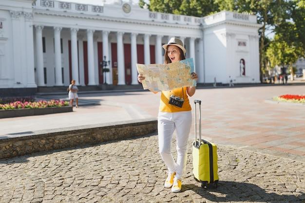 Mulher de turista viajante chocado no chapéu de roupas casuais de verão amarelo com mala, olhando na rota de pesquisa de mapa da cidade na cidade ao ar livre. garota viajando para o exterior na fuga de fins de semana. estilo de vida da viagem de turismo.