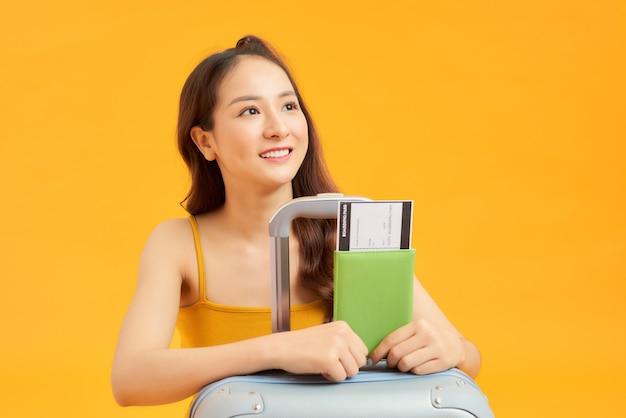 Mulher de turista viajante em roupas casuais de verão com seu passaporte, bagagem isolada em fundo laranja amarelo.