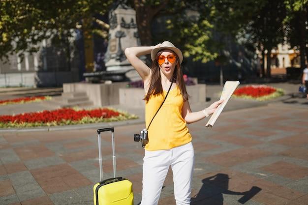 Mulher de turista viajante engraçado em roupas amarelas, óculos de coração laranja com câmera fotográfica de mapa de cidade mala na cidade ao ar livre. garota viajando para o exterior para viajar no fim de semana. estilo de vida da viagem de turismo.