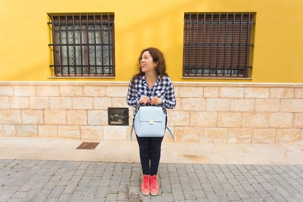 Mulher de turista viajante engraçado espantado em roupas casuais segura o saco. estilo de vida da viagem de turismo.