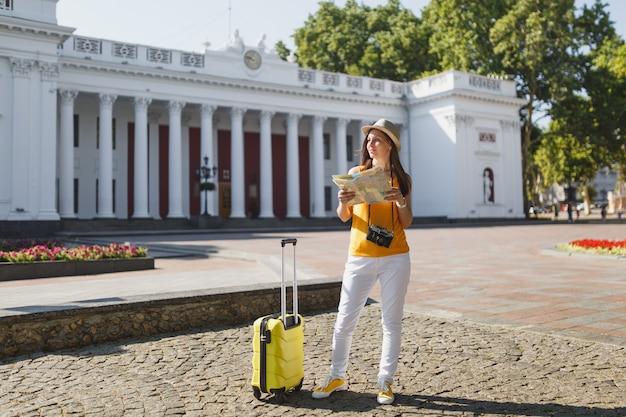 Mulher de turista viajante no chapéu de roupas casuais de verão amarelo com mala segurando o mapa da cidade olhando de lado na cidade ao ar livre. garota viajando para o exterior para viajar na escapadela de fins de semana. estilo de vida da viagem de turismo.