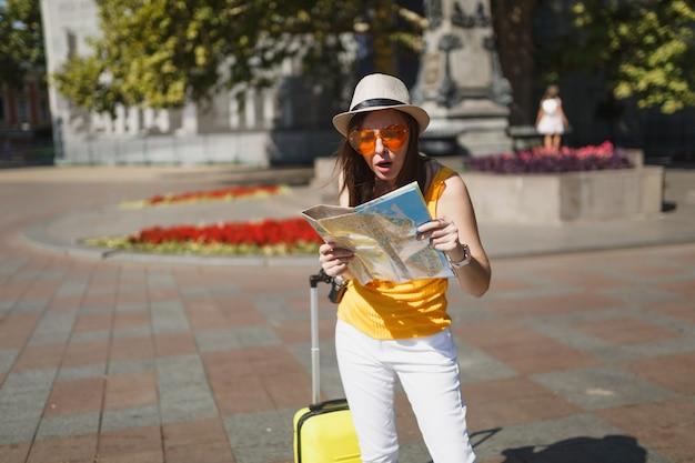 Mulher de turista viajante perplexo chocado em óculos de coração laranja com rota de pesquisa de mala no mapa da cidade na cidade ao ar livre. garota viajando para o exterior para viajar na escapadela de fins de semana. estilo de vida da viagem de turismo.