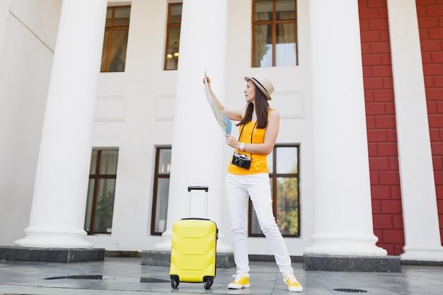 Mulher de turista viajante perplexo em roupas casuais de verão amarelo e chapéu com mala, olhando no mapa da cidade na cidade ao ar livre. garota viajando para o exterior para viajar no fim de semana. estilo de vida da viagem de turismo.
