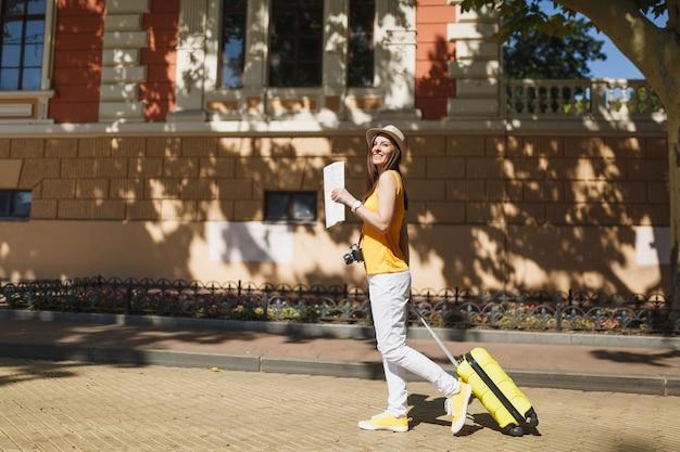 Mulher de turista viajante rindo em roupas casuais de verão amarelo, chapéu com mapa da cidade mala andar na cidade ao ar livre. garota viajando para o exterior para viajar no fim de semana. conceito de estilo de vida de viagem de turismo.