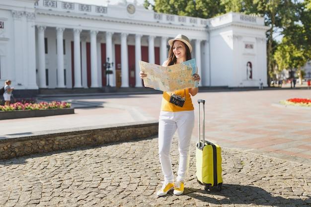 Mulher de turista viajante rindo no chapéu de roupas casuais de verão amarelo com mala olhando na rota de pesquisa de mapa da cidade na cidade ao ar livre. garota viajando para o exterior em uma escapadela de fim de semana. estilo de vida da viagem de turismo.