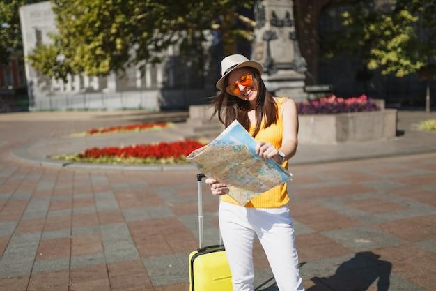 Mulher de turista viajante rindo no chapéu, roupa amarela, óculos de coração laranja com mala segurar mapa da cidade na cidade ao ar livre. garota viajando para o exterior para viajar no fim de semana. estilo de vida da viagem de turismo.