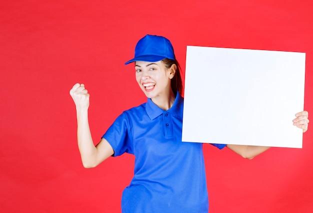 Mulher de uniforme azul e boina, segurando uma mesa de informações quadrada branca e mostrando sinal de sucesso com a mão.