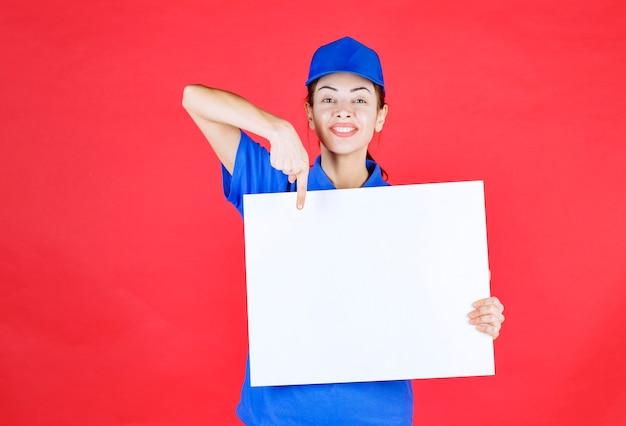 Mulher de uniforme azul e boina segurando uma mesa de informações quadrada branca e se sentindo positiva.