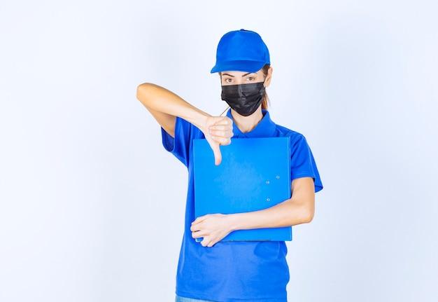 Mulher de uniforme azul e máscara facial preta, segurando uma pasta azul e mostrando o polegar para baixo o sinal.