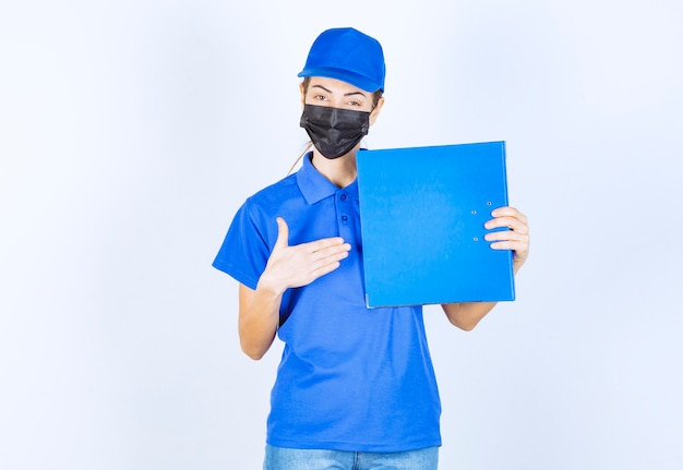 Mulher de uniforme azul e máscara facial preta segurando uma pasta de relatórios azuis.