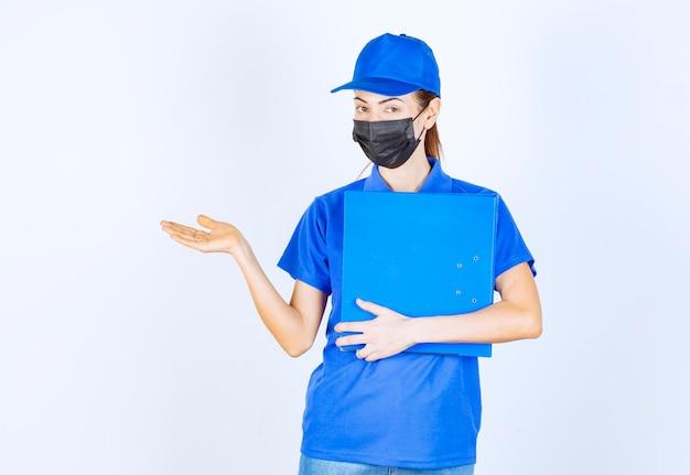 Mulher de uniforme azul e máscara preta, segurando uma pasta azul e apontando para alguém à parte.