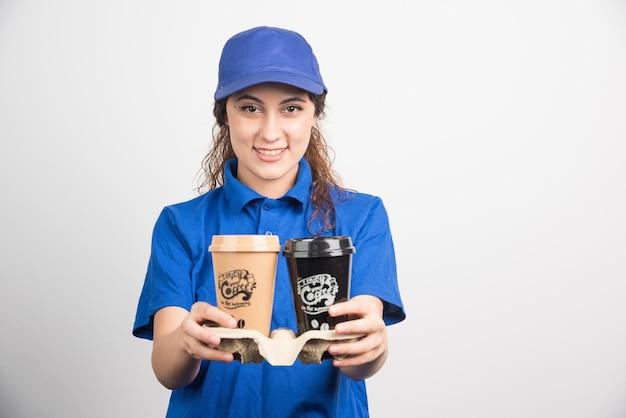 Mulher de uniforme azul segurando duas xícaras de café em branco.