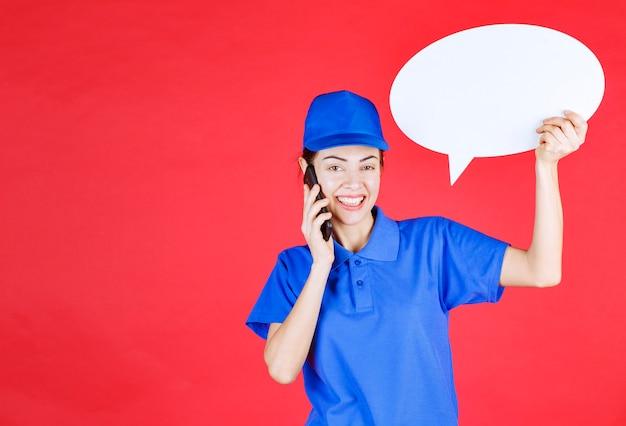 Mulher de uniforme azul segurando uma placa de ideia oval e falando ao telefone.