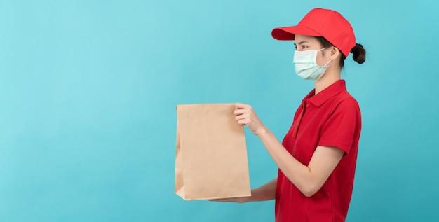 Mulher de uniforme de camisa de boné vermelho, usando máscara facial e mão segurando um saco de papel artesanal em branco marrom.