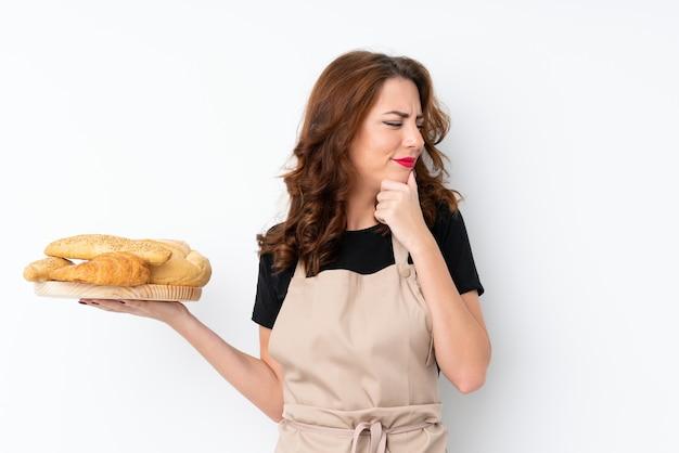 Mulher de uniforme de chef. padeiro feminino segurando uma mesa com vários pães, pensando uma idéia e olhando de lado