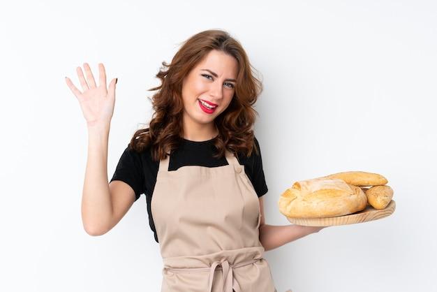 Mulher de uniforme de chef. padeiro feminino segurando uma mesa com vários pães, saudando com a mão com expressão feliz