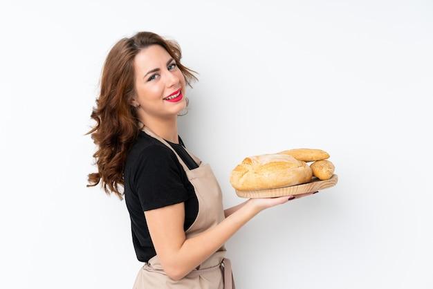Mulher de uniforme de chef. padeiro feminino segurando uma mesa com vários pães, sorrindo muito